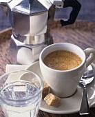 Tasse Espresso mit Wasserglas und Maschine im Hintergrund