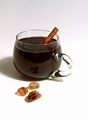 Mulled wine in glass with cinnamon stick, candy sugar beside it