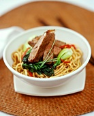 Lamb fillet with chili and pak choi on Chinese egg noodles
