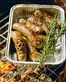 Home-made lamb sausages in aluminium dish