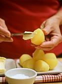 Person streicht Butter auf Pellkartoffel,davor Schälchen Salz