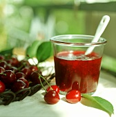 Cherry jam in jar, fresh cherries beside it