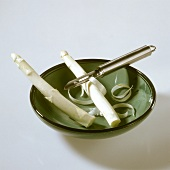 Two spears of white asparagus with vegetable peeler