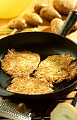 Three potato pancakes (rosti) in a frying pan