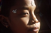 Asian woman with rice as face decoration (temple festival, Bali)