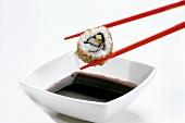 Stäbchen mit Ura-Maki-Sushi (Inside-Out-Roll) über Sojasauce