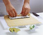 Hands rolling Nigiri sushi