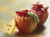 Baked apple with marzipan caterpillar
