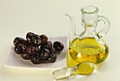Small carafe of olive oil and olives on a plate