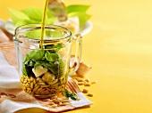Ingredients for pesto in a measuring jug