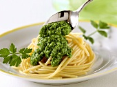 Spooning parsley and almond pesto on to pasta