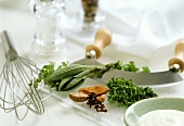 Still life with herbs, whisk and mezzaluna