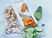 Gemüsehobel mit Champignon-, Möhren- und Gurkenscheiben