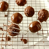 Rolling soft chocolate truffles over lattice with special fork