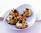 Piped poppy seed biscuits decorated with black cherries