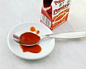 Sieved tomatoes in tetrapack and on plate with spoon
