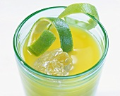 Orange drink with ice cubes and lime peel