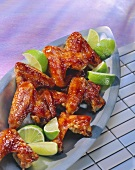 Barbecued chicken wings with lime wedges