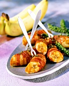 Fried bananas in bacon with green pepper and ketchup