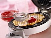 Sweet waffle with icing sugar and jam on waffle iron