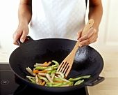 Frying vegetables in wok