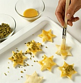 Decorating biscuits with egg yolk glaze and pistachios
