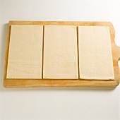 Frozen puff pastry on chopping board