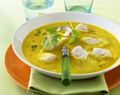 Exotic fish soup with curry and coriander leaves