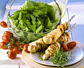 Barbecued bread sticks, basket of lettuce, tomatoes behind