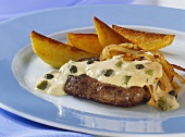 Steak and onions with caper sauce and fried potatoes