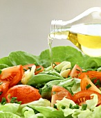 Drizzling mixed salad with oil