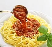 Pouring tomato sauce over spaghetti
