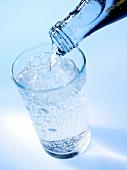 Mineralwasser aus der Flasche ins Glas gießen
