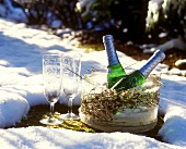 Two piccolo bottles & champagne glasses in wintry landscape