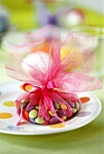 Coloured chocolate beans packed in tulle as Easter gift