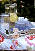 Tray with cup and lemonade on a cushion in the open air