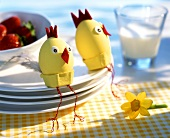 Two Easter eggs decorated as chicks sitting on pile of plates