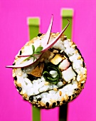California maki with swordfish on chopsticks