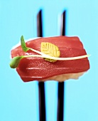 Nigiri-sushi with tuna on chopsticks