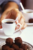 Hand holding a cup of espresso, rum truffles in front
