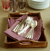 Cutlery on a tray, glasses and pile of plates behind