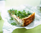 A piece of ham and cheese quiche with herbs