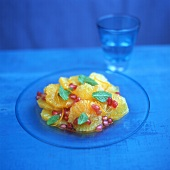 Orange salad with pomegranate in blue light