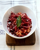 Apple and red cabbage on white platter