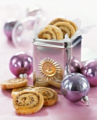 Spiral-shaped nut biscuits in and in front of biscuit tin