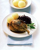 Duck leg with red cabbage and dumplings