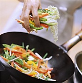 Putting Asian vegetables into wok