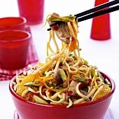 Chopsticks holding Asian stir-fry with meat, vegetables, oranges