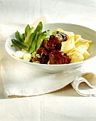 Lamb ragout with noodles in orange butter and mangetouts