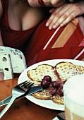 Waffeln mit Kirschkompott, Frau im Hintergrund (Grainy Effect)